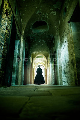 A semi-silhouette of a mystery Victorian woman walking down the decaying corridore of a workhouse or prison.