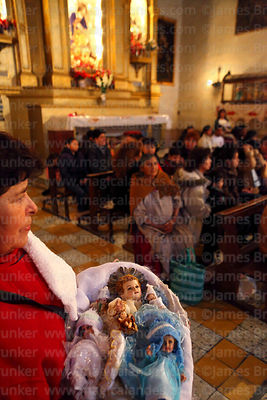 Woman holding baby Jesus figures in church during mass for Reyes (Epiphany, January 6th), La Paz, Bolivia