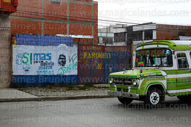 Local public bus called a micro driving past slogans on wall showing support for Movimiento al Socialismo MAS political party...