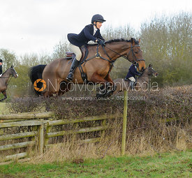 Zoe Gibson jumping a hedge with the The Belvoir Hounds at Ingarsby Hall 3/2