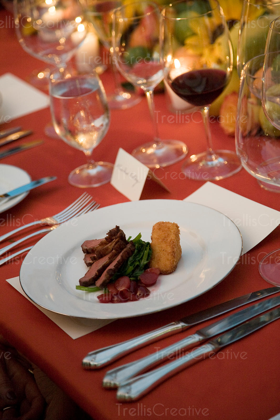 Rare beef filet with warm grapes and polenta served on a beautifully decorated table