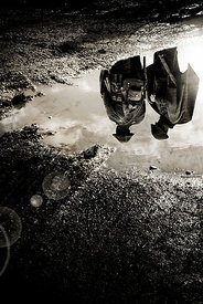 An atmospheric image of two British soldiers, standing, reflected in a muddy puddle in WW1.