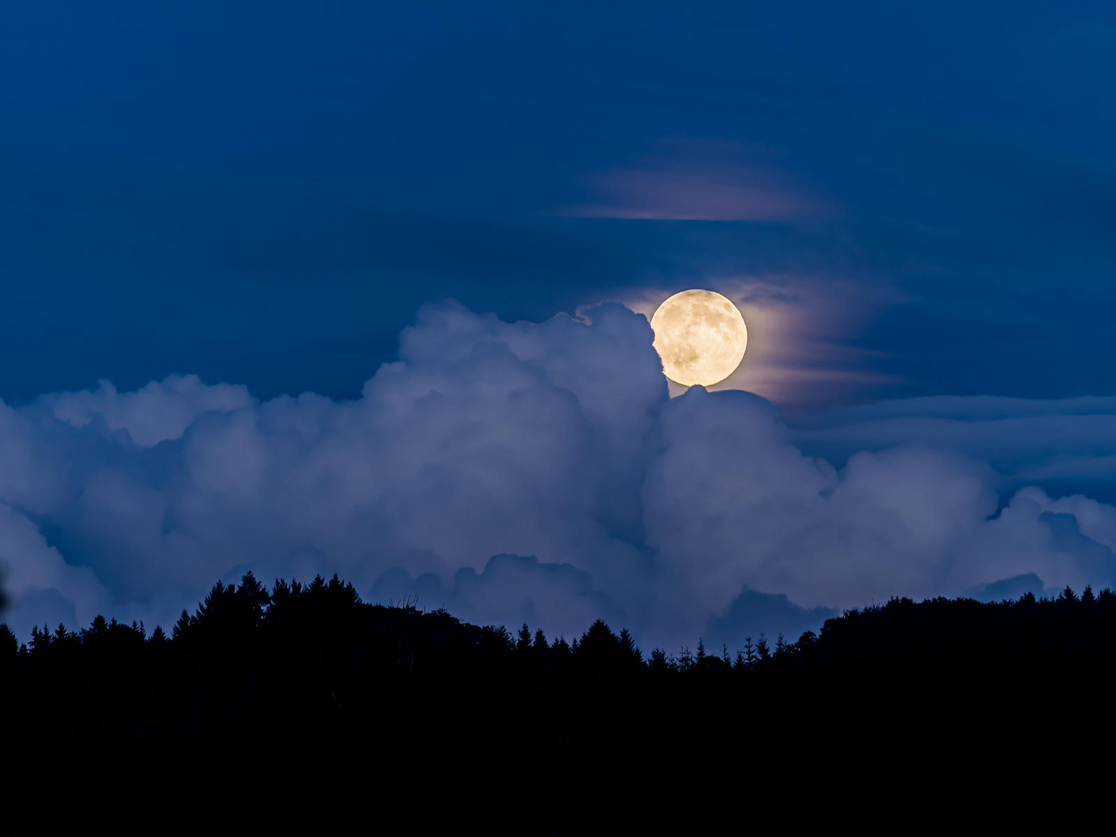 Moon rise in twilight behind clouds