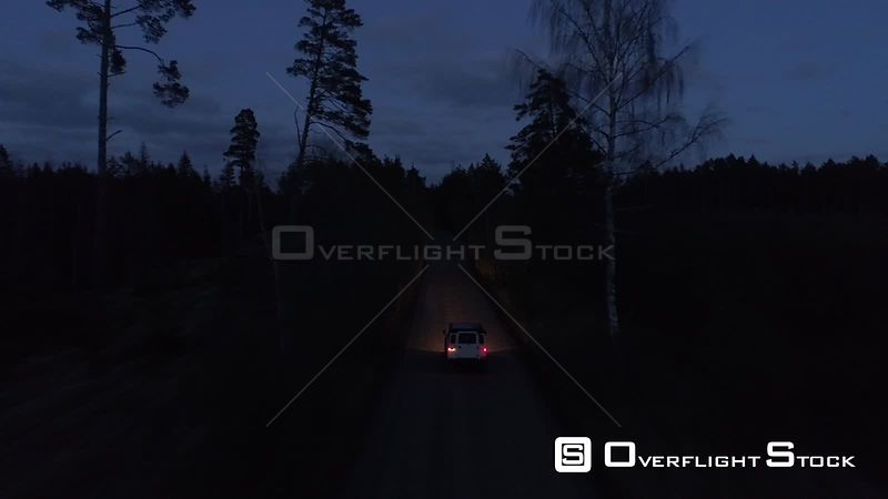 Aerial drone tracking shot of a 4x4 off road vehicle driving in night on a gravel road Latvia