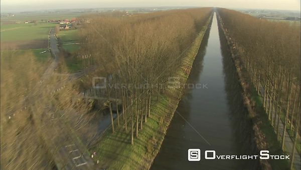 Low flight between treelined banks of a canal near Bruges, Belgium