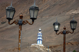 Rusting street lamps and old clock tower on hillside above Pisagua , Region I , Chile
