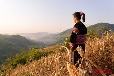 Woman of Lisu tribe looking at landscape at sunrise