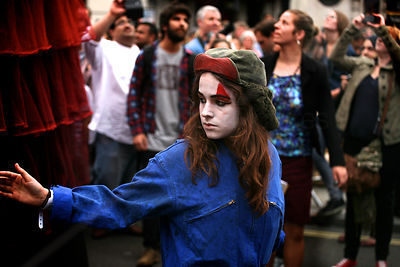 Young Woman with a Painted Face working with Les Poupées Géantes Performers in Piccadilly Circus London