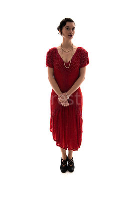 A vintage 1920s - 1930s woman in a red dress and pearls – shot