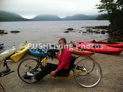 Young woman using a handcycle on the edge of a lake