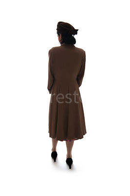 A silhouette of a 1940's woman in a hat and coat, walking away – shot from eye-level.