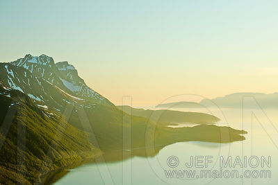 Beautiful midnight sun light on mountain and fjord
