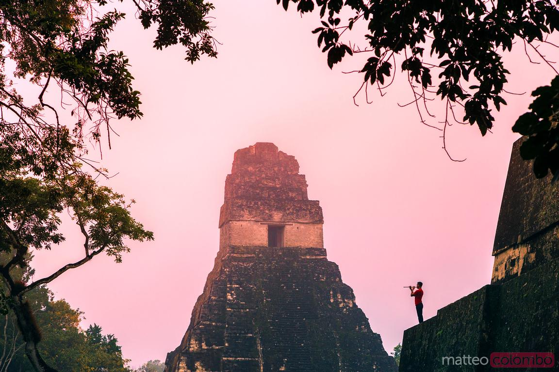 Dawn at Temple of the Jaguar with local man playing a flute, Tikal, Guatemala