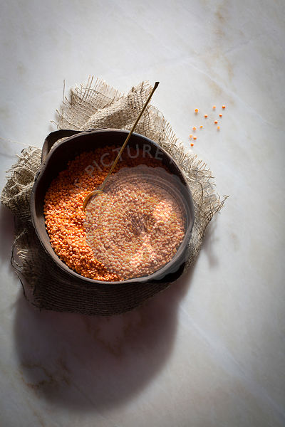 Masoor dal/ Red/Orange lentils in a ceramic bowl on a marble table on top view