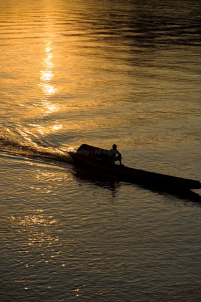 Laos mekong river silhouette of a small boat traveling downstream