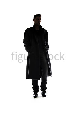 A Figurestock image of a mystery man, in silhouette, in a long black winter coat, walking towards camera – shot from low level.
