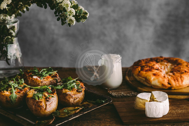 Baked stuffed potatoes with cheese, vegetables, sour cream and rucola on wooden table Rustic background. Copy space