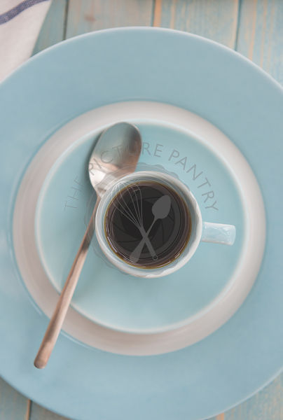 A black coffee in a blue espresso cup.