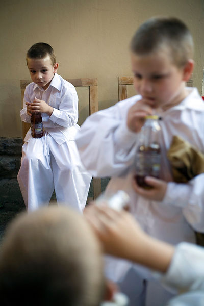 Hungary - Pecs - Boys backstage in traditional costume drink soda from bottles
