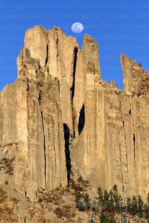 Nearly full waxing moon rising above rock formations of Valle de las Animas, La Paz, Bolivia