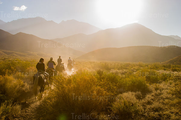 Riding on horseback into a dusty canyon