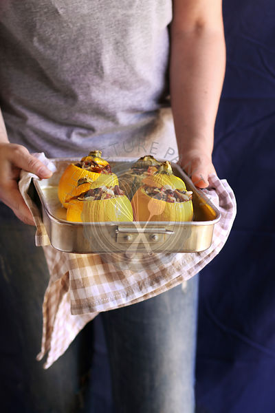 Female hands holding a pan with roasted stuffed zucchini