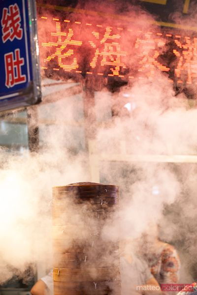 Street food in China: cooking dumplings by steam