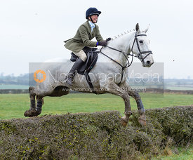 Tessa Vestey jumping a hedge on Greenall's