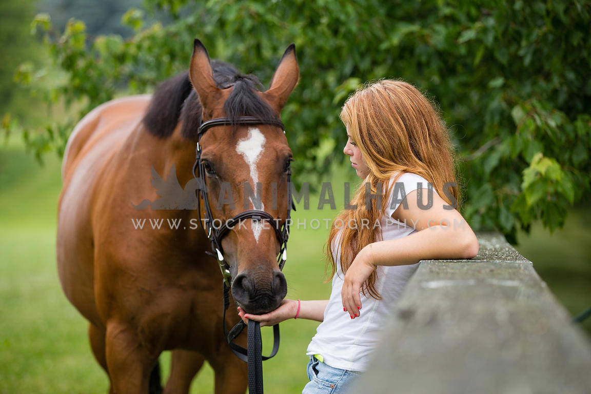girl leaning on fence with horse