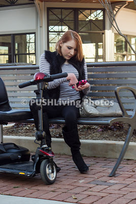 Woman sitting on  a park bench texting with her mobility scooter
