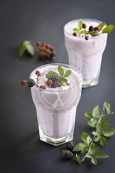 Two glasses with blackberry smoothie decorated with fresh blackberries