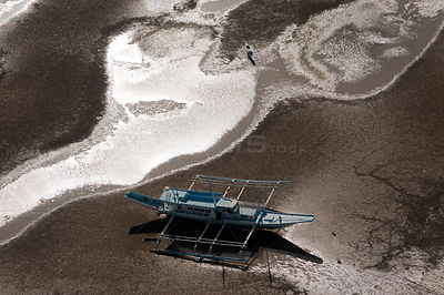 Aerial view of outrigger boats moored in the coastal mudflats, stuck at low-tide waiting for high tide, Sarangani Bay, Philip...