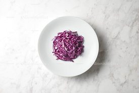 Dish with purple cabbage sliced in white marble background