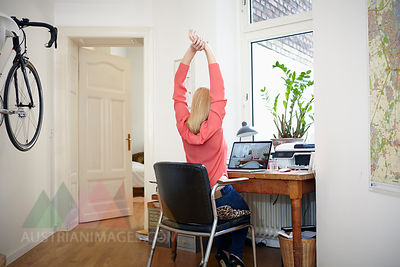 Woman sitting at desk in her workroom stretching
