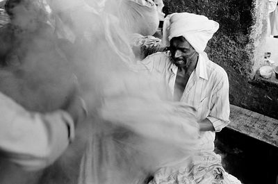 A Dhobi or washermen pulls at some boiling sheets.