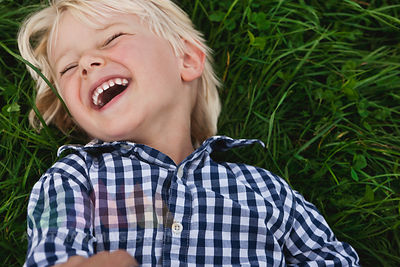 Germany, Cologne, Boy (2-3 Years) lying on grass and laughing