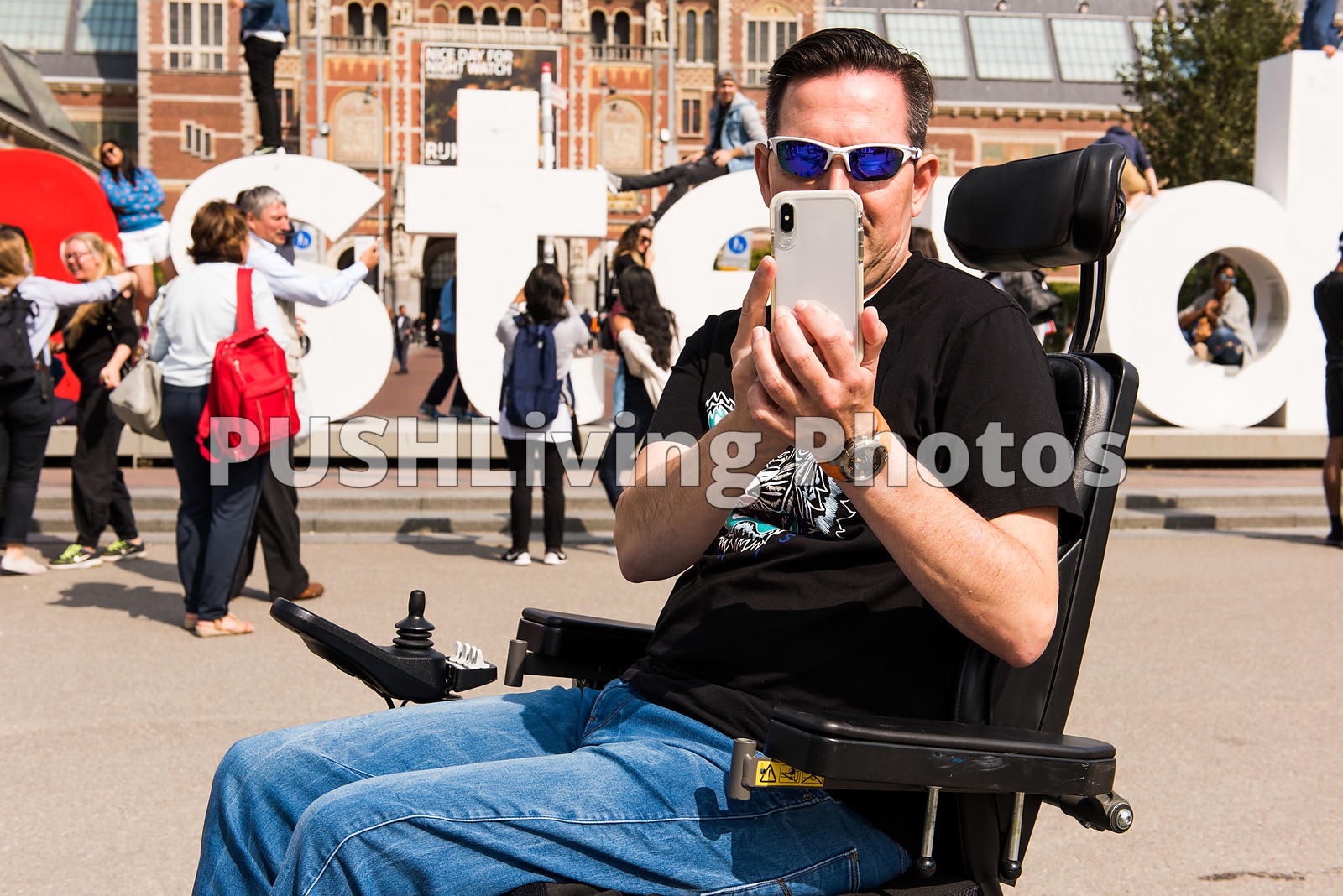 Man using a power wheelchair taking a selfie in Amsterdam
