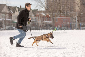man running with dog in city park