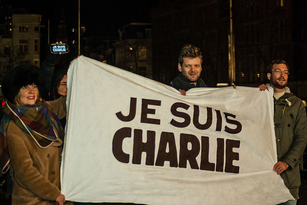 Amsterdam, Netherlands 2015-01-08: Three demonstrants holding a banner 'Je suis Charlie' .
