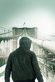 An atmospheric image of a hooded mystery man standing on the Brooklyn Bridge in New York City.