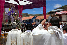 Priest taking photo of the Virgen de la Candelaria after central mass, Puno, Peru