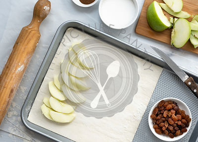 Preparation of apple strudel, apple slices layered on a sheet of pastry on a baking tray.