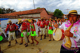 Erquero musician playing erke (horn) and caja (drum) accompanies dancers wearing traditional dress during Carnival parades, S...