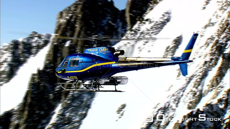 A helicopter rising to fly above peaks in the French Alps