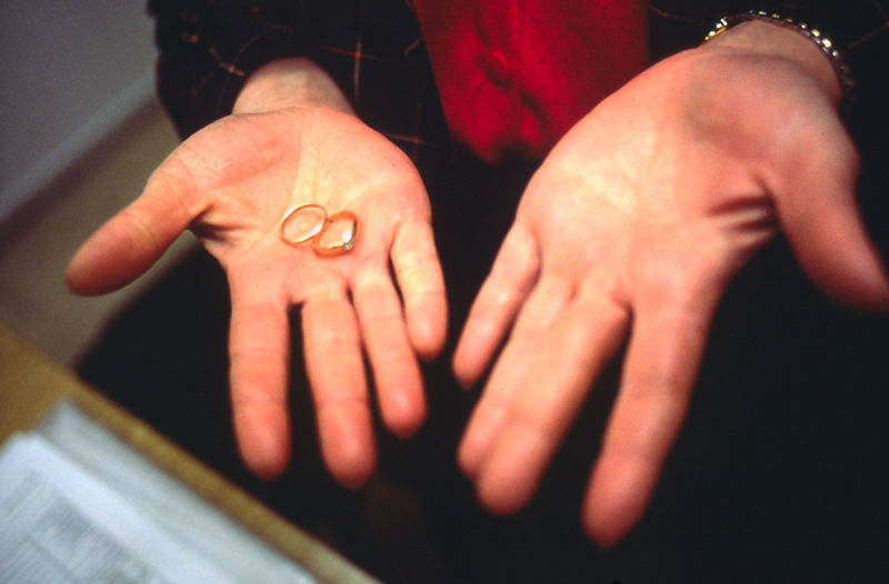 A woman holds her wedding rings on the day of her divorce