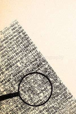 magnifying glass and typewriter text on ancient paper texture
