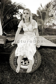 An atmospheric image of a mystery girl lsitting on the back of a truck.