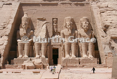 Tourists having a group photograph taken in front of the facade of the Sun Temple at Abu Simbel, Egypt