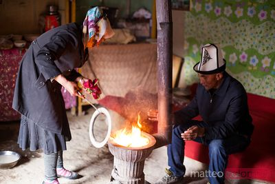 Kyrgyz man and woman heating the stove inside the yurt
