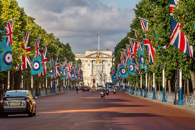 Buckingham Palace in early morning light with RAF flags and Union Jacks flying in The Mall